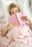 Senior Woman Relaxing In Bed Reading Diary Stock Photography