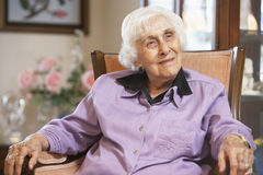 Senior woman relaxing in chair stock photos
