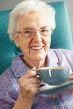 Senior Woman Relaxing In Chair With Hot Drink Stock Image