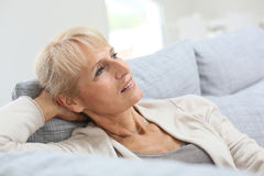 Senior woman relaxing on couch Royalty Free Stock Photos