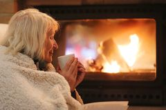 Senior woman relaxing by fireplace stock images