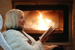 Senior woman relaxing by fireplace Royalty Free Stock Image