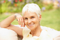 Senior Woman Relaxing In Garden Royalty Free Stock Image