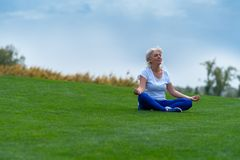 Senior woman meditating on green grass royalty free stock images
