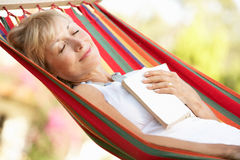 Senior Woman Relaxing In Hammock Stock Photography