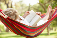 Senior Woman Relaxing In Hammock With Book Stock Image