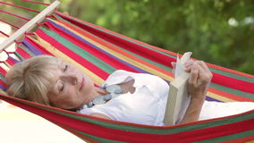 Senior Woman Relaxing In Hammock With Book Royalty Free Stock Image