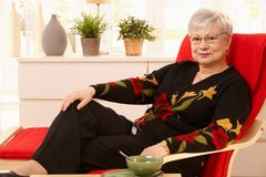 Senior woman relaxing at home. Sitting in armchair, having tea Stock Image