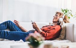 Senior woman relaxing at home. Senior woman relaxing at home, listening to music Royalty Free Stock Photo