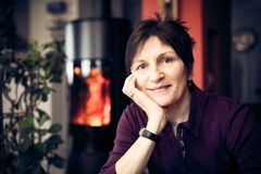 Senior Woman Relaxing At Home. In front of the fireplace Royalty Free Stock Photo