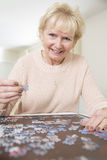 Senior Woman Relaxing With Jigsaw Puzzle At Home Royalty Free Stock Photo