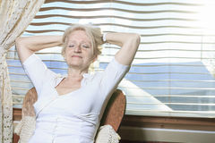 Senior woman relaxing on the kitchen stock photography