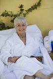 Senior Woman Relaxing On Lounge Chair Royalty Free Stock Image