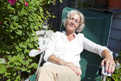 Senior woman relaxing on lounge chair in garden Stock Photography