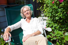 Senior woman relaxing on lounge chair in garden Stock Photo