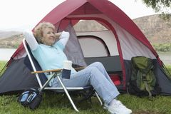 Senior Woman Relaxing Outside A Tent Stock Images