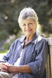 Senior Woman Relaxing On Park Bench Stock Images