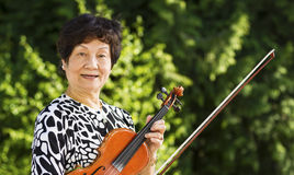 Senior Woman Relaxing from playing the violin outdoors Royalty Free Stock Photos