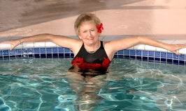 Senior woman relaxing in the pool. An attractive smiling senior woman relaxing by the edge of the pool Royalty Free Stock Image