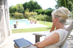 Senior woman relaxing by the pool. Senior woman reading book by swimming-pool Stock Photo