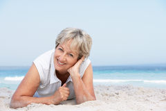Senior Woman Relaxing On Sandy Beach. Smiling At Camera Royalty Free Stock Photo