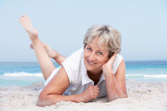 Senior Woman Relaxing On Sandy Beach Stock Photo