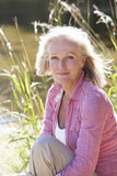 Senior Woman Relaxing By Side Of Lake Stock Photography