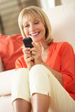 Senior Woman Relaxing On Sofa Sending Text Message. Smiling royalty free stock photography