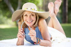 Senior Woman Relaxing In Summer Garden Stock Photo