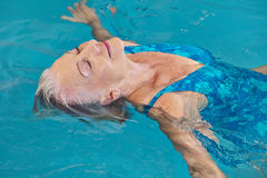 Senior woman relaxing in swimming pool Royalty Free Stock Images