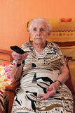 Senior woman and remote control. Senior woman changing the TV channel with a remote control Stock Photos
