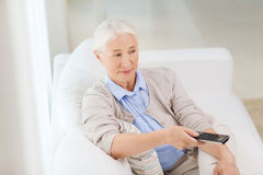 Senior woman with remote watching tv at home. Technology, television, age and people concept - senior woman watching tv and changing channel with remote control Stock Photos