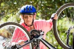 senior woman is repairing her bike Royalty Free Stock Photos
