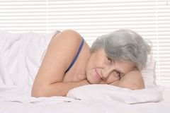 Senior woman  resting in a bedroom Royalty Free Stock Photos