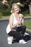 Senior Woman Resting And Drinking Water After Exercise Royalty Free Stock Photos