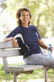 Senior Woman Resting After Exercise In Park Stock Photo
