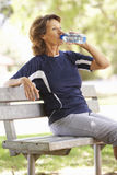 Senior Woman Resting After Exercise In Park Stock Image