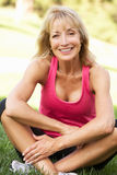 Senior Woman Resting After Exercising In Park Stock Photos
