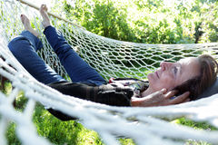 Smiling mature woman in hammock. Senior woman resting and listening to music in a hammock Royalty Free Stock Photo