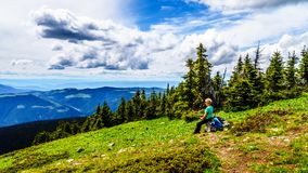 Senior Woman resting during a hike on Tod Mountain near the alpine village of Sun Peaks in the Shuswap Highland. S of British Columbia, Canada royalty free stock photography