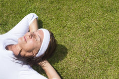 Senior woman resting relaxed on lawn Stock Photography