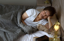 Senior woman restless at nighttime while trying to sleep. Restless senior woman staring at bed stand during night time. Insomnia concept royalty free stock image