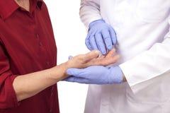Senior woman with Rheumatoid arthritis visit a doctor. Isolated on white Royalty Free Stock Photo