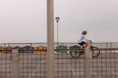 Senior woman riding bicycle on promenade. Side view of senior woman riding bicycle on promenade at beach royalty free stock image