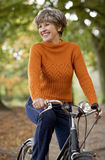 A senior woman riding a bicycle, smiling, Royalty Free Stock Image