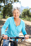 Senior woman riding through countryside Stock Photos