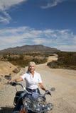 Senior woman riding motorcycle on desert road Stock Photos