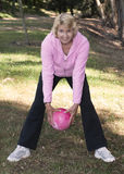 Senior woman rolling ball in park Royalty Free Stock Photography