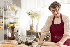 Senior woman rolling pizza dough Stock Photography