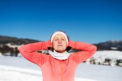 Senior woman runner resting in winter nature, eyes closed and hands behind head. stock images
